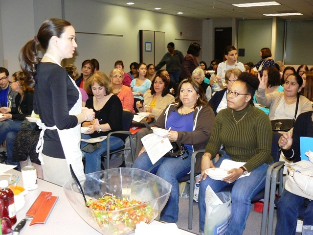 Extension Agent Katie Strong answers questions after audience samples a Smoky Black Bean and Corn Salad prepared during Fairfax County Administrative Resource Team Conference workshop.