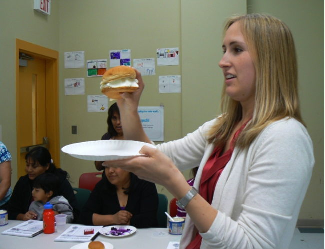 "Jessica Forsty holds up a ""blubber burger"" filled with Crisco to illustrate the amount of unhealthy fat in one participant's favorite fast food meal."
