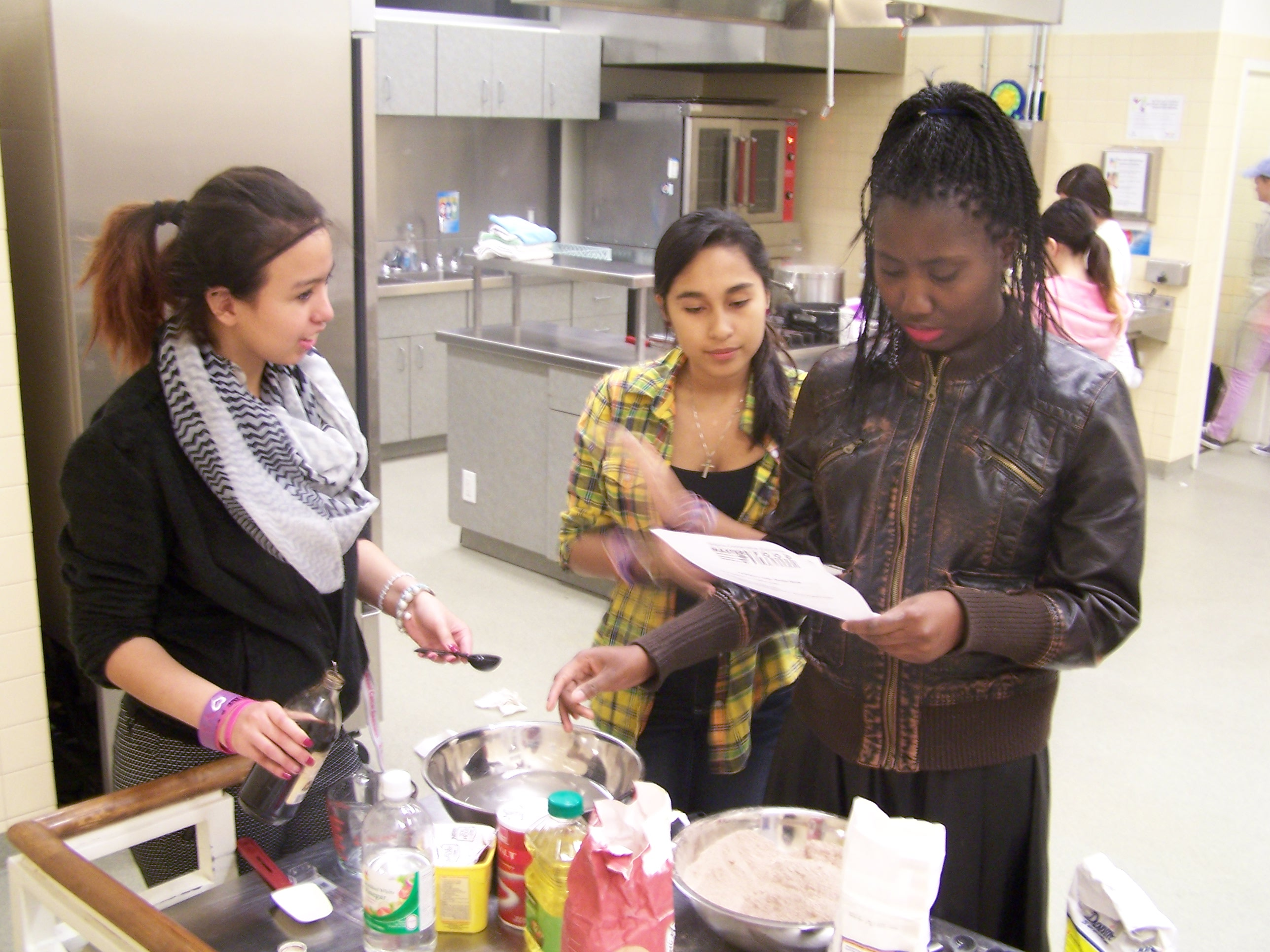 Teens check a recipe while making chocolate cake