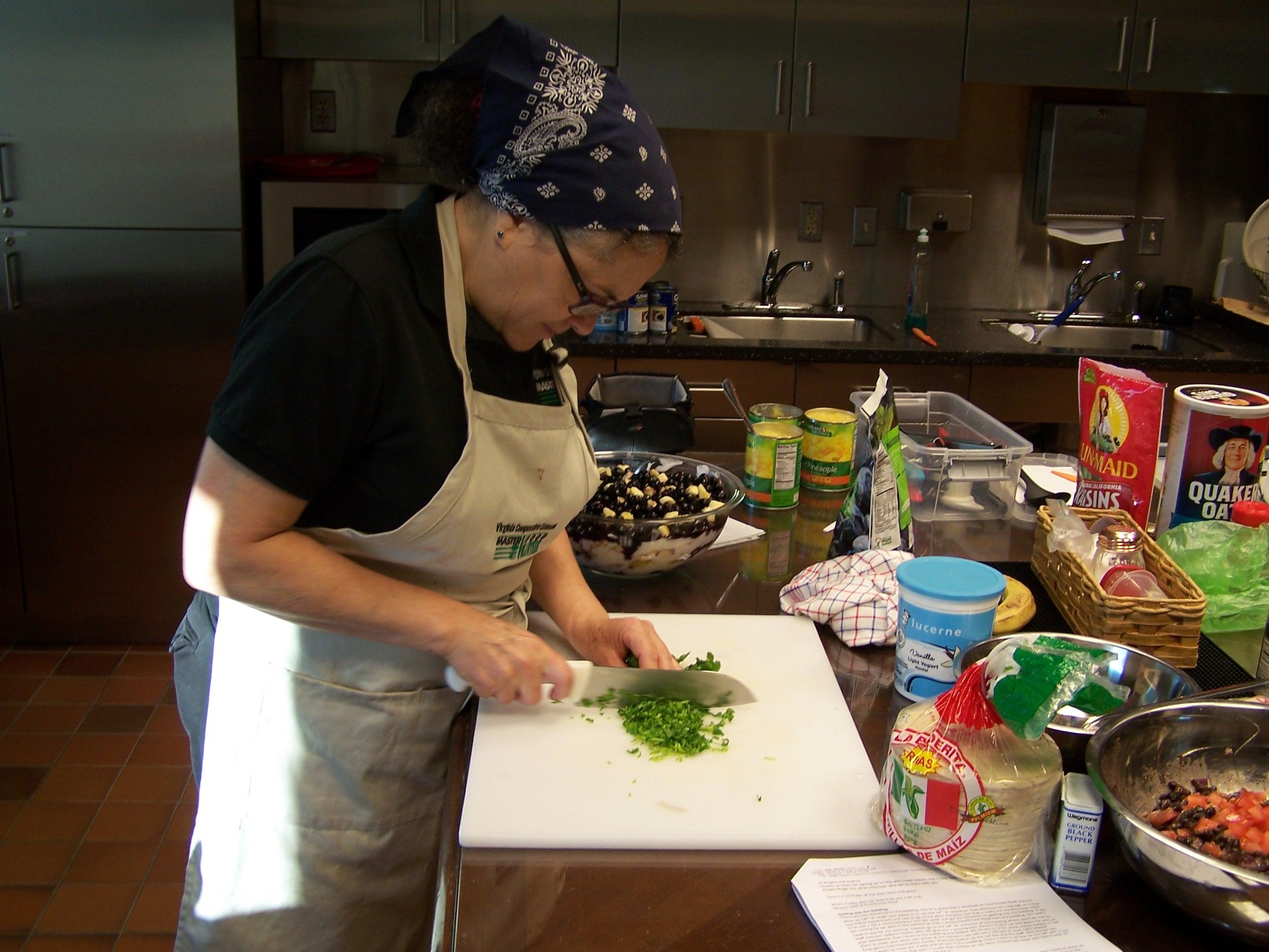 Master Food Volunteer Angela Braga chops cilantro for breakfast buritos.