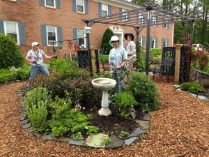 garden with bird bath and group of master gardeners